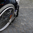 Stock Photo: Wheelchair on cobblestones