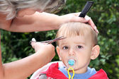 Hair cutting first one-year-old child — Stock Photo