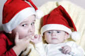 Child and newborn with Christmas hat — Stock Photo