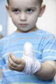 Blessé à la main gauche avec le garçon de bandage au coup de feu dans la maison — Photo