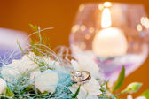 Wedding rings lying on white kytce a candle in a glass cup — Stock Photo