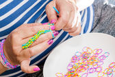 Women with colorful nails making a rubber loom — Stock Photo