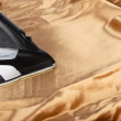 Steam iron on gold satin — Foto de stock #27583317
