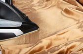 Steam iron on a gold satin — Stock Photo