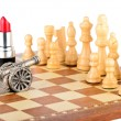 Stock Photo: Chessmen, lipstick and gun