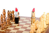 Two lipsticks on the battlefield of chess — Stock Photo