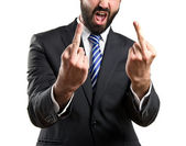 Young businessman doing the horn sign over white background — Stock Photo