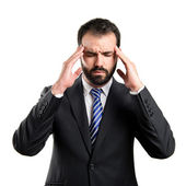 Young businessman with headache over white background — Stock Photo