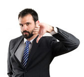 Young businessman with his thumb down over white background — Foto Stock