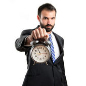 Young businessman holding an antique clock over white background — Stockfoto