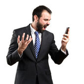 Young businessmen shouting to mobile over isolated background. — Stock Photo