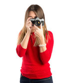 Girl taking a picture over white background — Stockfoto