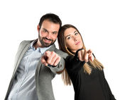 Couple pointing to the front over white background — Stock Photo