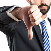 Young businessman with his thumb down over white background — Stock Photo