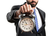 Businessman holding an antique clock over white background — Stock Photo