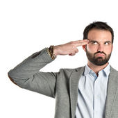 Young businessman making suicide gesture over white background — Stockfoto