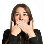 Pretty young girl with her mouth closed by her hands — Stockfoto