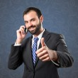 Young businessmen talking to mobile over blue vintage background. — Stock Photo