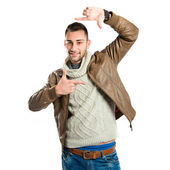 Young man doing a frame sign over white background — Stock Photo
