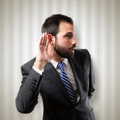 Young business man hearing something over textured background — Stock Photo