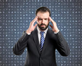 Young businessman with headache over blue background with icons — Photo