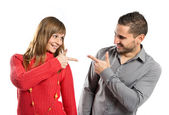 Couple pointing each other over white background — Stock Photo