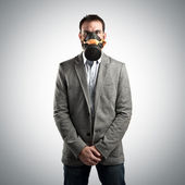 Young businessman with gas mask over grey background — Stock Photo