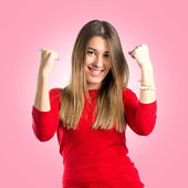 Young woman winner over pink background — Stockfoto