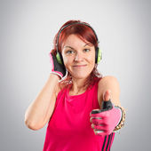 Young sport girl listening music over grey background — Stock Photo