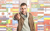 Young man pointing over background with flags — Stock Photo