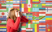 Young girl shouting over background with flags — Stock Photo