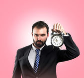 Young businessman holding an antique clock over pink background — Stock Photo