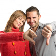 Foto de Stock  : Couple with their thumbs down over white background
