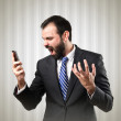 Young businessmen shouting to mobile over textured grey background. — Stock Photo