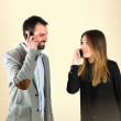 Couple talking to mobile over white background. — Stock Photo