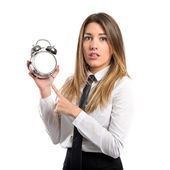 Young businesswoman holding an antique clock over white background — Stok fotoğraf