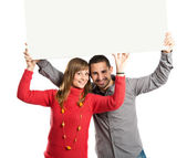 Couple holding placard over white background — Stok fotoğraf