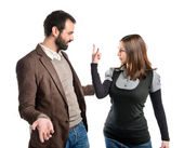 Girl doing the horn sign at her boyfriend over white background  — Stock Photo