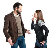 Young girl making silence gesture at her boyfriend over white background  — Stock fotografie