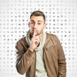 Young man making silence gesture over icons background — Stock Photo
