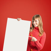 Young blonde girl holding placard over red background  — Stock Photo