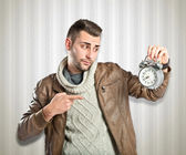 Young businessman holding an antique clock over textured background  — Stok fotoğraf