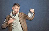 Young businessman holding an antique clock over vintage background  — Stock Photo