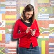 Young girl sending a message with her mobile over flags background — Stock Photo