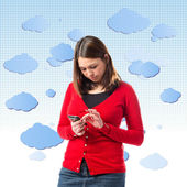 Young girl sending a message with her mobile over background with clouds. — Stock Photo