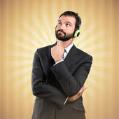 Young businessman listening music over ocher background — Stock Photo