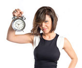 Pretty woman holding an antique clock over white background  — Zdjęcie stockowe