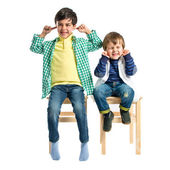 Boys covering his ears over white background.  — Stock Photo
