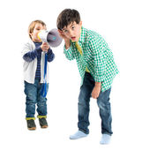 Kid shouting at his friend by megaphone over white background  — Zdjęcie stockowe