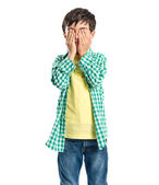 Boy covering his eyes over white background  — Foto Stock
